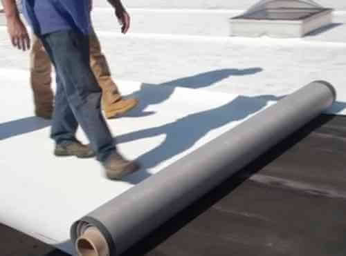 Workers installing flat roof base sheet