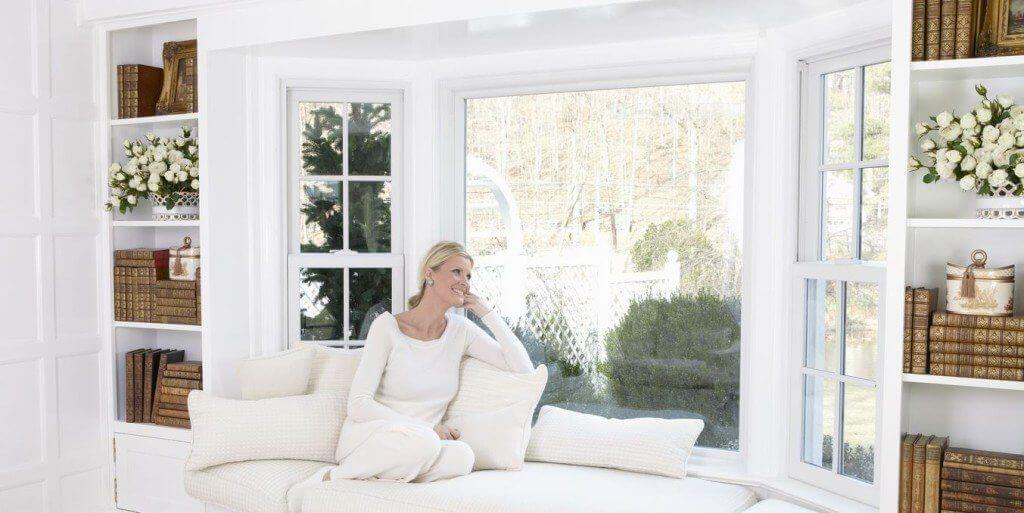 woman sitting and enjoying new replacement windows