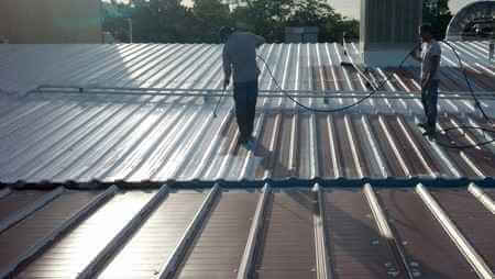 metal roof being sprayed with roof coating system